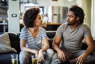 Young-African-American-couple-talking-in-the-living-room.-1128733022_1258x838-1024x683